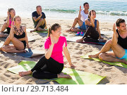 Купить «Sporty people practicing yoga on beach», фото № 29713484, снято 14 июня 2017 г. (c) Яков Филимонов / Фотобанк Лори