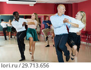 Купить «Young positive people dancing vigorous jive movements in dance studio», фото № 29713656, снято 4 октября 2018 г. (c) Яков Филимонов / Фотобанк Лори
