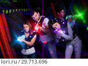 Купить «Young people playing laser tag in bright beams», фото № 29713696, снято 25 апреля 2018 г. (c) Яков Филимонов / Фотобанк Лори