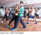 Купить «Group of young people dancing salsa together», фото № 29713924, снято 27 мая 2019 г. (c) Яков Филимонов / Фотобанк Лори