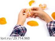 Купить «Подросток очищает мандарин от кожуры», фото № 29714960, снято 2 декабря 2018 г. (c) V.Ivantsov / Фотобанк Лори