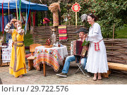 Купить «Russia, Khabarovsk, August 18, 2018: women and men in Russian-national costumes play folk musical instruments; balalaika and accordion», фото № 29722576, снято 18 августа 2018 г. (c) Катерина Белякина / Фотобанк Лори