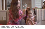 Купить «Beautiful Young Long-haired Mother Sits Next To Her Charming Daughter», видеоролик № 29723000, снято 22 июля 2019 г. (c) Pavel Biryukov / Фотобанк Лори