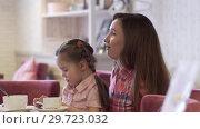 Купить «Side View - A Young Mother Is Holding Her Beautiful Little Daughter», видеоролик № 29723032, снято 20 мая 2019 г. (c) Pavel Biryukov / Фотобанк Лори