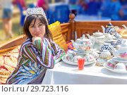Купить «Russia, Samara, July, 2018: A young beautiful brunette girl in Uzbek national attire sells tea sets at the fair.», фото № 29723116, снято 29 июля 2018 г. (c) Акиньшин Владимир / Фотобанк Лори