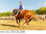 Купить «Russia, Samara, July, 2018: a Cossack girl rides a horse and performs tricks.», фото № 29723208, снято 29 июля 2018 г. (c) Акиньшин Владимир / Фотобанк Лори