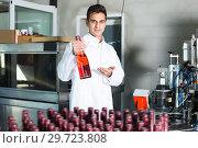 Купить «Male worker holding newly produced bottle», фото № 29723808, снято 21 сентября 2016 г. (c) Яков Филимонов / Фотобанк Лори