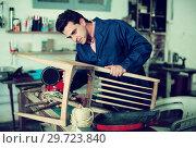 Купить «Carpenter repairing broken wooden furniture», фото № 29723840, снято 8 апреля 2017 г. (c) Яков Филимонов / Фотобанк Лори