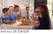 Купить «happy family having dinner party at home», видеоролик № 29724624, снято 8 января 2019 г. (c) Syda Productions / Фотобанк Лори