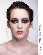 Купить «Closeup macro portrait of female face. Girl with perfect skin, green pistachio colour eyes and violet - black smoky eyes make-up.», фото № 29729236, снято 22 марта 2018 г. (c) Serg Zastavkin / Фотобанк Лори