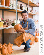 Happy male artisan holding ceramics in hands. Стоковое фото, фотограф Яков Филимонов / Фотобанк Лори