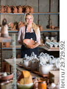 Купить «Portrait of glad woman pottery worker with ceramic crockery», фото № 29729592, снято 28 января 2020 г. (c) Яков Филимонов / Фотобанк Лори