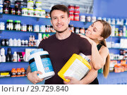 Купить «Loving athletic couple holding plastic jars of sport food supplements in shop interior», фото № 29729840, снято 12 апреля 2018 г. (c) Яков Филимонов / Фотобанк Лори