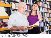 Купить «Man looking book, granddaughter chatting by phone», фото № 29734760, снято 28 июня 2017 г. (c) Яков Филимонов / Фотобанк Лори