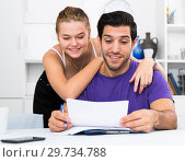 Happy man and woman reading mail together at home. Стоковое фото, фотограф Яков Филимонов / Фотобанк Лори