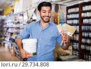 Купить «Man standing amongst racks in paint store with brushes and paint», фото № 29734808, снято 13 сентября 2017 г. (c) Яков Филимонов / Фотобанк Лори