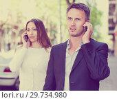 Купить «Young couple speaking on phones», фото № 29734980, снято 11 апреля 2017 г. (c) Яков Филимонов / Фотобанк Лори