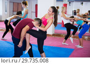 Купить «Group of female are doing box exercises with instructor», фото № 29735008, снято 8 октября 2017 г. (c) Яков Филимонов / Фотобанк Лори
