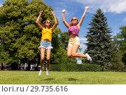 Купить «happy teenage girls jumping at summer park», фото № 29735616, снято 19 июля 2018 г. (c) Syda Productions / Фотобанк Лори