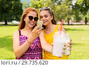 teenage girls with smartphone and shakes in park. Стоковое фото, фотограф Syda Productions / Фотобанк Лори
