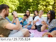Купить «friends with drinks photographing at summer picnic», фото № 29735824, снято 17 июня 2018 г. (c) Syda Productions / Фотобанк Лори