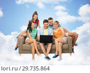 Купить «friends with laptop computer on sofa over clouds», фото № 29735864, снято 30 июня 2018 г. (c) Syda Productions / Фотобанк Лори