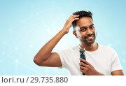 Купить «smiling indian man with trimmer touching his hair», фото № 29735880, снято 27 октября 2018 г. (c) Syda Productions / Фотобанк Лори