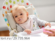 Купить «little baby girl eating in highchair at home», фото № 29735964, снято 25 августа 2018 г. (c) Syda Productions / Фотобанк Лори