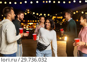 Купить «friends with drinks dancing at rooftop party», фото № 29736032, снято 2 сентября 2018 г. (c) Syda Productions / Фотобанк Лори