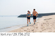 Купить «couple in sports clothes running along on beach», фото № 29736212, снято 1 августа 2018 г. (c) Syda Productions / Фотобанк Лори