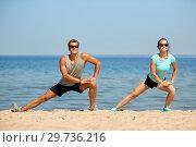 Купить «smiling couple stretching legs on beach», фото № 29736216, снято 1 августа 2018 г. (c) Syda Productions / Фотобанк Лори