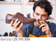 Young man repairing shoes in workshop. Стоковое фото, фотограф Elnur / Фотобанк Лори