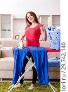 Купить «Young beautiful woman ironing at home», фото № 29742140, снято 30 октября 2018 г. (c) Elnur / Фотобанк Лори