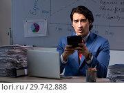 Купить «Young elegant financial specialist working in the office night t», фото № 29742888, снято 25 октября 2018 г. (c) Elnur / Фотобанк Лори