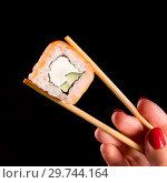 Японская кухня. Суши ролл. Фото для меню азиатская кухня. Роллы с лососем держит в руке на палочках девушка с красными ноглями. Стоковое фото, фотограф Евгений Бобков / Фотобанк Лори