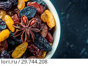 Купить «White ceramic bowl with Assortment of Raisins, yellow, blue, black, golden raisin and anise on black background. Healthy snack. Vega Food. Food mix background, top view, copy space, banner.», фото № 29744208, снято 28 марта 2018 г. (c) Евгений Бобков / Фотобанк Лори
