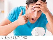 Купить «Man trying contact lenses at home», фото № 29744624, снято 6 августа 2018 г. (c) Elnur / Фотобанк Лори