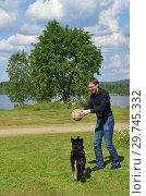 Купить «Young man plays with dog with ball in meadow. Finnish Lapland», фото № 29745332, снято 15 июля 2018 г. (c) Валерия Попова / Фотобанк Лори
