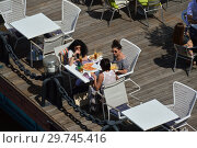 Купить «Вид сверху на отдыхающих людей за столиками кафе «Оливковый пляж» на Пушкинской набережной. Район Якиманка. Город Москва», эксклюзивное фото № 29745416, снято 19 июня 2016 г. (c) lana1501 / Фотобанк Лори