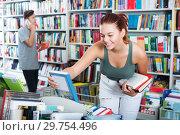 Купить «Girl looking for new literature», фото № 29754496, снято 16 сентября 2016 г. (c) Яков Филимонов / Фотобанк Лори