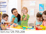 Купить «Children dough play in daycare centre. Kids mold from plasticine in kindergarten. Little students knead modeling clay with hands in preschool.», фото № 29755208, снято 23 марта 2019 г. (c) Оксана Кузьмина / Фотобанк Лори