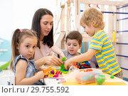 Купить «Tutor teaches children handcraft at kindergarten or playschool», фото № 29755592, снято 26 марта 2019 г. (c) Оксана Кузьмина / Фотобанк Лори