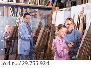 Купить «Smiling female assistance girl pupil during painting», фото № 29755924, снято 21 августа 2019 г. (c) Яков Филимонов / Фотобанк Лори