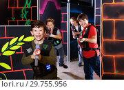 Купить «Emotional teen boy with laser pistol playing laser tag with friends on dark labyrinth», фото № 29755956, снято 24 октября 2018 г. (c) Яков Филимонов / Фотобанк Лори