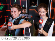 Купить «Girl and boy playing laser tag», фото № 29755980, снято 24 октября 2018 г. (c) Яков Филимонов / Фотобанк Лори