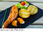 Купить «Fried salmon steak with baked potatoes, egg yolk, vegetables», фото № 29756216, снято 22 января 2019 г. (c) Яков Филимонов / Фотобанк Лори
