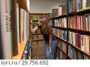Купить «Девушка ищет книгу в библиотеке», фото № 29756692, снято 15 января 2019 г. (c) Иванов Алексей / Фотобанк Лори