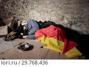 Купить «Man sleeping on the street under German flag», фото № 29768436, снято 21 октября 2018 г. (c) Сергей Новиков / Фотобанк Лори