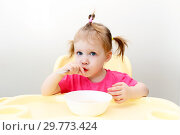Lovely little girl eating soup at home kitchen. Стоковое фото, фотограф ivolodina / Фотобанк Лори