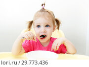 Cute little girl eating soup at home kitchen. Стоковое фото, фотограф ivolodina / Фотобанк Лори